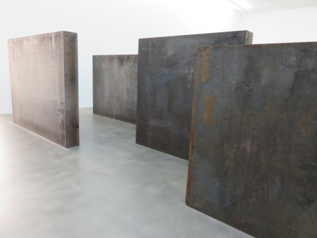 Steel Slabs (2015) by Richard Serra, an artwork reflecting the postmodern belief that art is essentially meaningless and so can be jobbed out and made to order, like industrial supplies