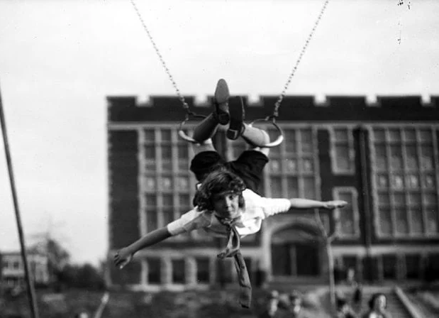 A child swinging from an old-school playground